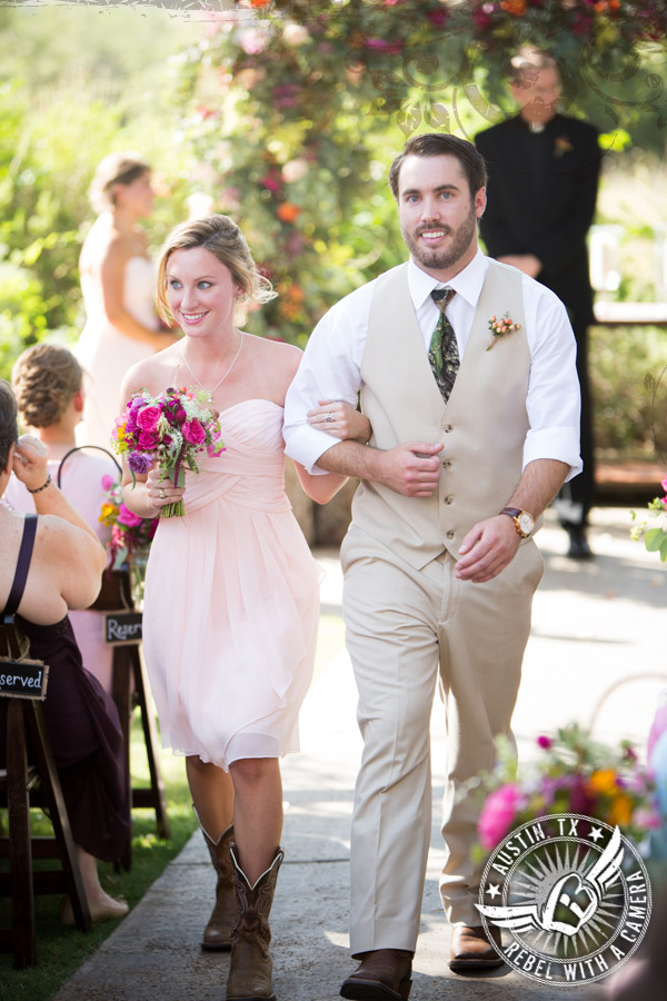 Bridesmaid and groomsman walk out at end of wedding ceremony at Vista West Ranch