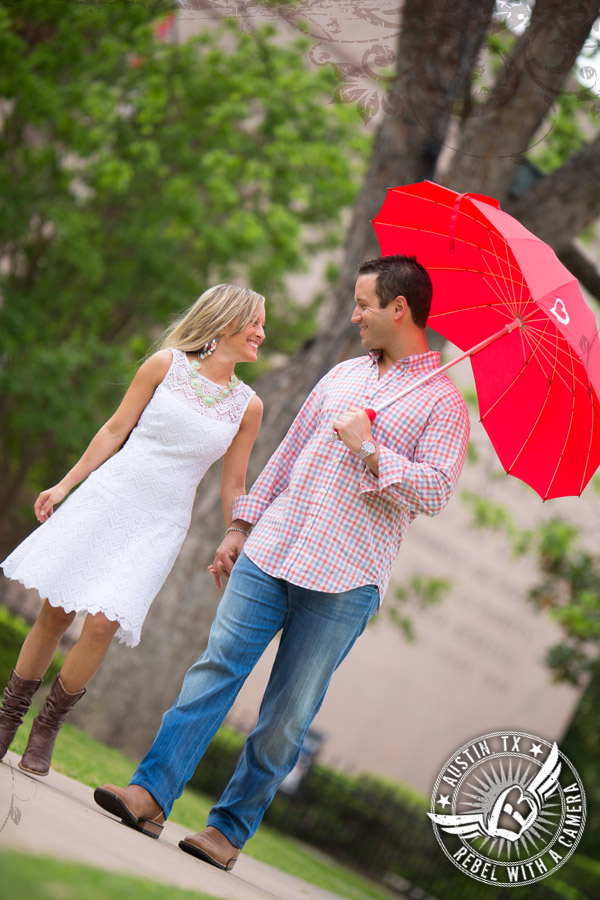 Downtown Austin engagement portraits walking with a red umbrella