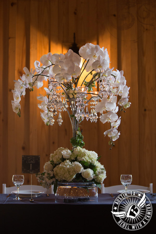 Rustic glam white orchid wedding table centerpiece by Brenda Abbott Floral Design at Gabriel Springs Event Center in Georgetown, Texas