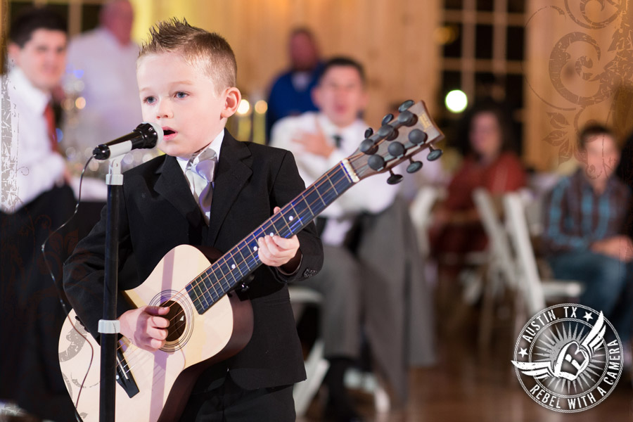 Ring bearer plays guitar at wedding reception at Gabriel Springs Event Center in Georgetown, Texas