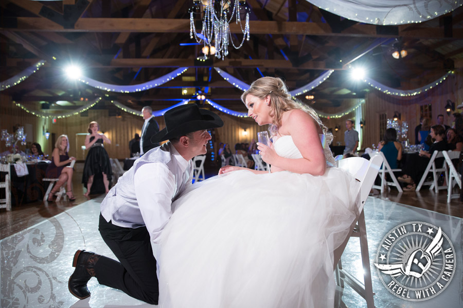 Groom removes the garter from the bride at Gabriel Springs Event Center in Georgetown, Texas