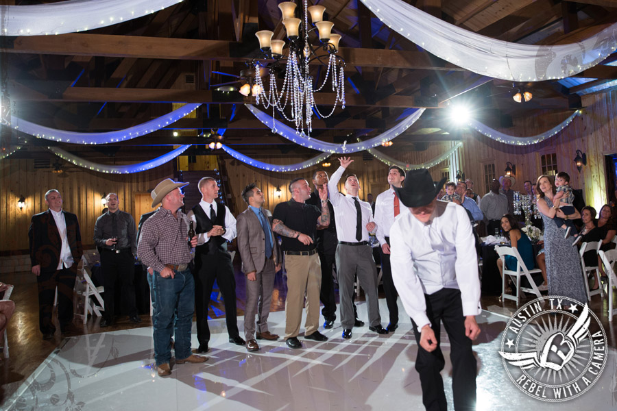 Groom throws the garter at Gabriel Springs Event Center in Georgetown, Texas
