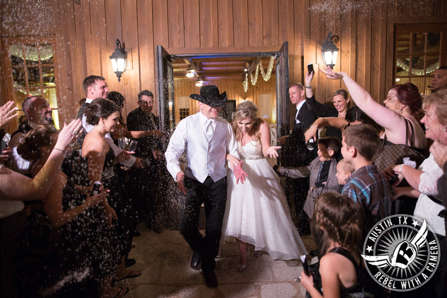 Bride and groom exit the wedding and guests throw birdseed at Gabriel Springs Event Center in Georgetown, Texas
